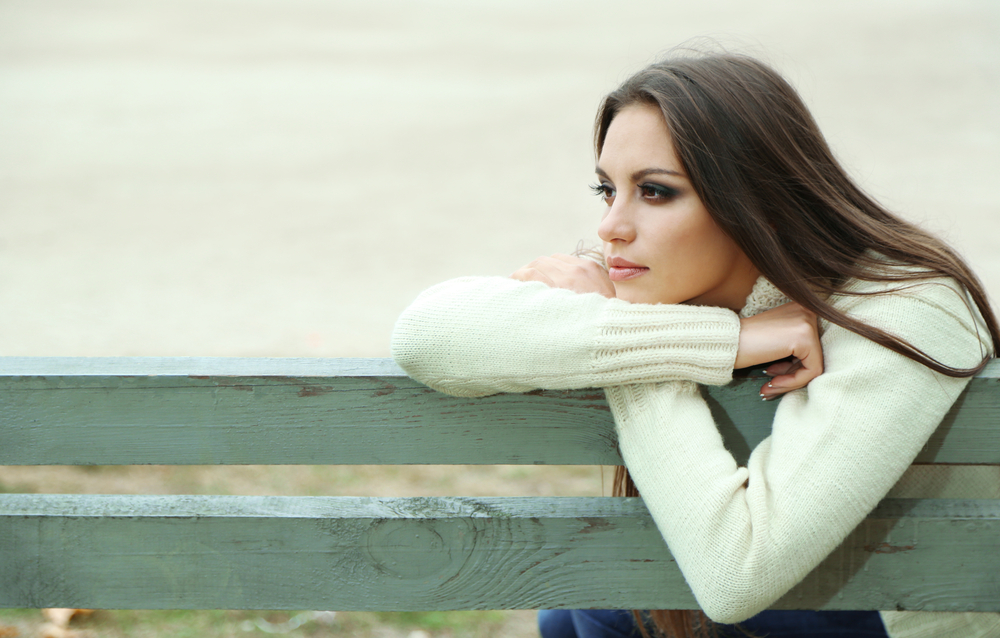 A woman is sitting alone on a bench.