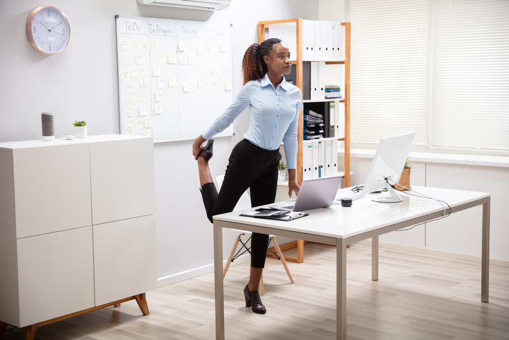 A woman stretching in her office on break.